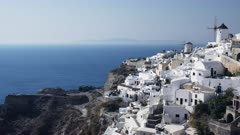 wide angle pan to the right of the windmills and houses in oia on the island of santorini, greece