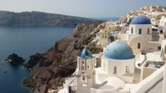 panning shot of the famous three blue domes at oia on the island of santorini, greece