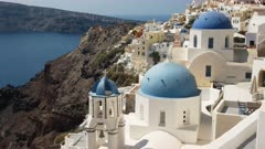zoom in on the three blue church domes in oia on the island of santorini, greece