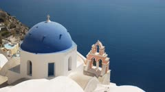 a blue church dome, pink arch and bells at oia on the island of santorini, greece