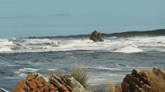 wild surf breaks at arthur river mouth, as seen from edge of the world, on the west coast of tasmania, australia