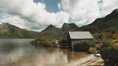 a summer shot of the historic boat shed at dove lake with tasmania's cradle mountain in the background