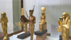 panning shot of golden statuettes from the tomb of tutankhamun in egypt