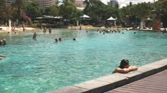 the view looking west of people enjoying the artificial beach and pool at south bank in brisbane, queensland