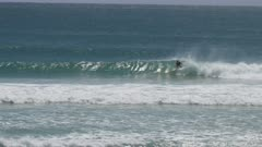 wide view of a surfer on their backhand at kirra on the gold coast of queensland, australia