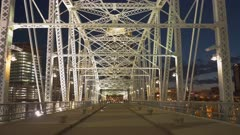 a three axis gimbal shot walking across shelby st pedestrian bridge in nashville, tennesse at night