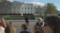 a group of protesters sing outside the white house in washington d.c. as security officers watch on