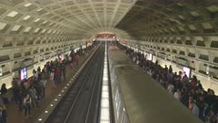 high angle shot of a train pulling into gallery place metro station in washington d.c.