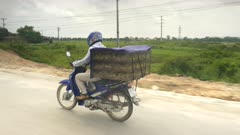 tracking shot of baby ducks being transported in a cage on a motorbike in vietnam