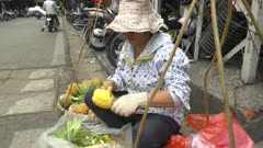 wide view of a woman cutting pineapples on a street in the old quarter of hanoi, vietnam
