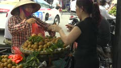 a woman sells fruit to a customer from a bicycle cart in the old quarter of hanoi, vietnam