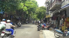 a panning shot of traffic on a street in the old quarter of hanoi, vietnam