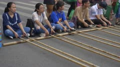 close up of several vietnamese youth moving bamboo poles for a tinikling game near hoan kiem lake in hanoi, vietnam