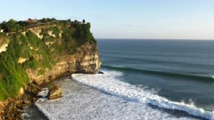 sunset close up looking east of cliffs and surf at uluwatu temple on bali, indonesia