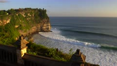 a sunset shot of the surf and uluwatu temple with a stone wall in the foreground- uluwatu temple is located on the indonesian island of bali