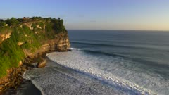 a wide shot of the cliffs and uluwatu temple at sunset on bali, indonesia