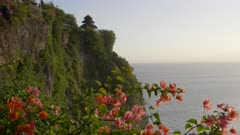 late afternoon shot of bali's uluwatu temple with bougainvillea flowers in the foreground