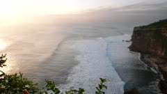 uluwatu temple at sunset with sun shining on spray from breaking waves at the island of bali, indonesia