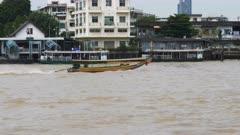 4K 60p tracking shot of a longtail boat on the chao phraya river in bangkok, thailand