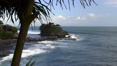 pura tanah lot temple framed by a pandanus tree on the indonesian island of bali