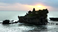 a wide high angle shot at sunset of tanah lot temple on the island of bali