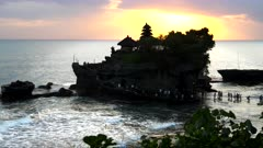 beautiful orange sunset shot of pura tanah lot temple at high tide on bali
