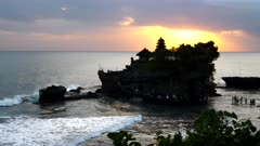 tourists wading out to visit the cave of tanah lot temple at sunset on bali