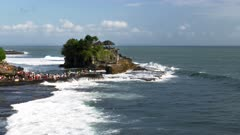 a wave breaks in front of pura tanah lot temple on the island of bali
