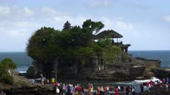 tourists visiting tanah lot temple during high tide on the island of bali, indonesia