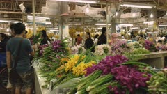 two thai shoppers inspect orchids at pak khlong talat flower market in bangkok, thailand
