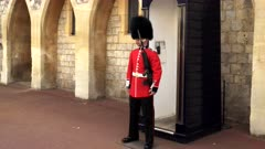 a queen's guard on duty at windsor castle near london, england