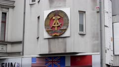 historic east german coat of arms on a building at checkpoint charlie in berlin, germany