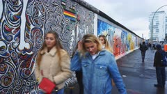 a gimbal steadicam clip of four female tourists walking past the berlin wall in germany
