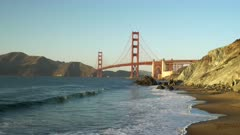 a sunset zoom in view of the golden gate bridge from marshall beach in san francisco, usa