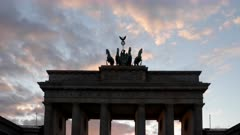 a sunset close up of a silhouetted quadriga on the brandenburg gate in berlin, germany
