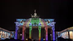 a rainbow colored reichstag dome is projected onto the brandenburg gate in berlin, germany