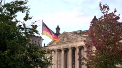 the reichstag building and a german flag framed by trees in berlin, germany