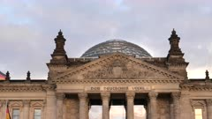 a close up shot of the reichstag building's pediment and dome in berlin, germany