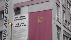 a zoom in shot of a replica soviet flag hanging on a wall near checkpoint charlie in berlin, germany