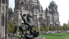 close up of the lion fighter staute at the altes museum with berlin cathedral in the distance