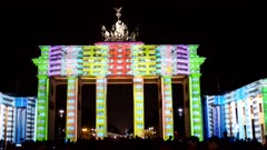 the brandenburg gate lit up with colored lights during the festival of light show in berlin, germany