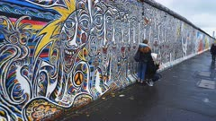 a gimbal shot walking past tourists posing for a photograph beside the berlin wall in germany