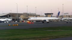 early morning shot of a united airlines plane being towed to the terminal at boston airport