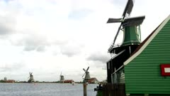 a green windmill at zaanse schans near amsterdam, netherlands