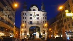night shot of johannes gutenberg monument on lugeck square in city of vienna, austria with the wastenrot insurance headquaters building in the background