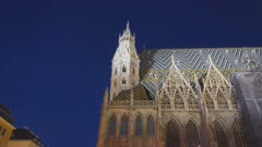 a night tilt down shot of the exterior of st stephen's cathedral in vienna, austria