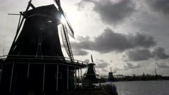 sun shines behind several windmills at zaanse schans near amsterdam, netherlands