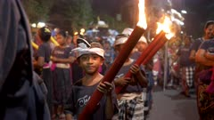 close up of a boy holding a burning torch in the new year street parade in bali, indonesia