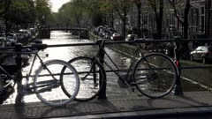 bicycles silhouetted on a bridge over a canal in amsterdam, netherlands