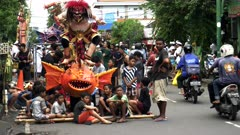 a group of children wait on the street with their ogoh ogoh statue prior to the new year parade at kuta on bali